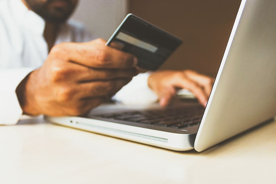 Hombre con tarjeta de crédito en la computadora
